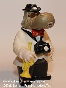 """Dresdner Dixieland-Maskottchen """"Dixie"""" als Werbefigur mit umgehängter Praktica-Kamera"""